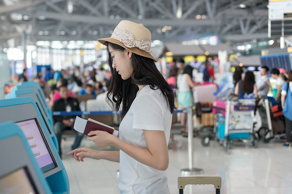 Young Asian woman using self check-in kiosks in airport