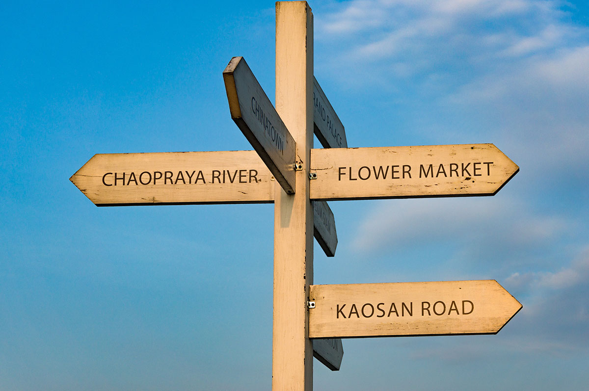 Bangkok street sign with directions to Chaopraya river, Kaosan road, flower market and Chinatown with blue sky on the background. Travel directory pointer with copy space