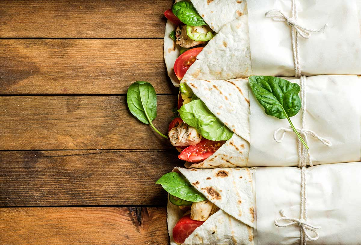 Healthy lunch snack. Tortilla wraps with grilled chicken fillet and fresh vegetables on rustic wooden background. Top view, copy space